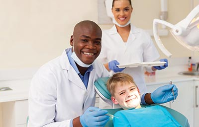 A dentist with his dental assistand and young patient