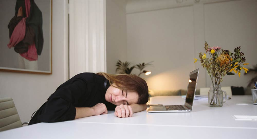 A young woman fallen asleep while studying at her computer