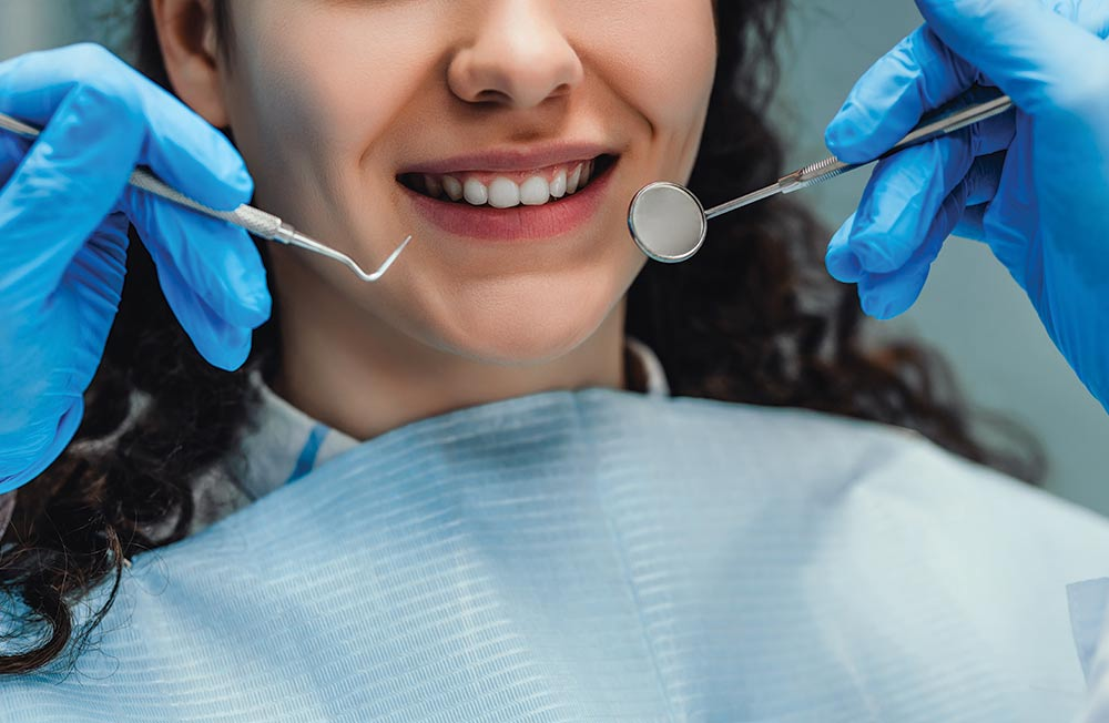 A girl getting a dental exam smiles